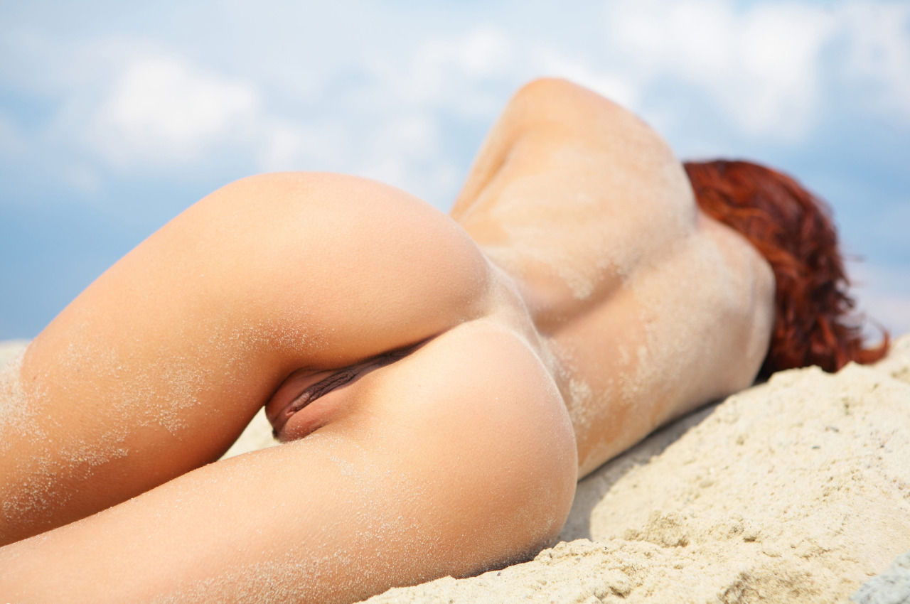 Redhead stretched out in the sand showing her tight pussy