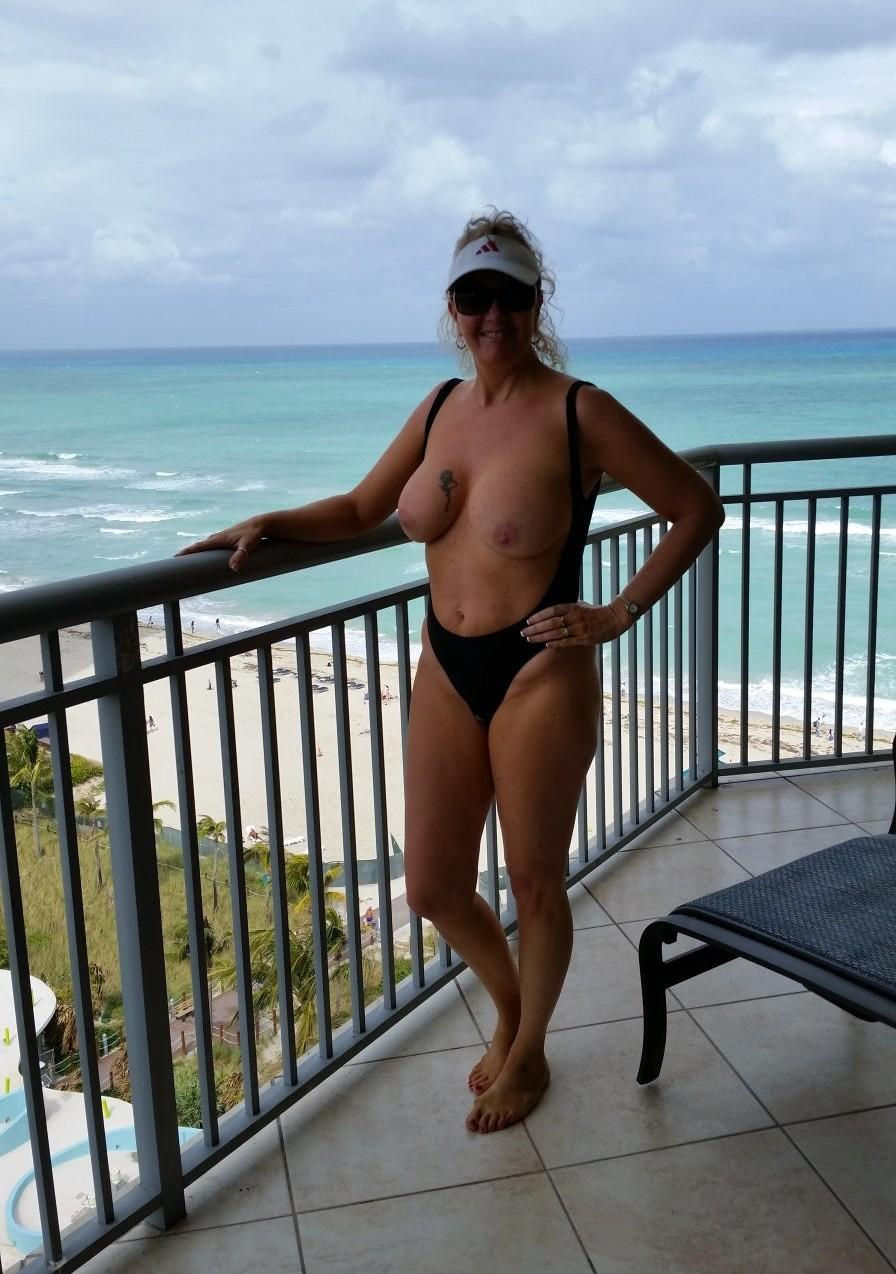 Mature woman without a bra relaxes on a hotel balcony