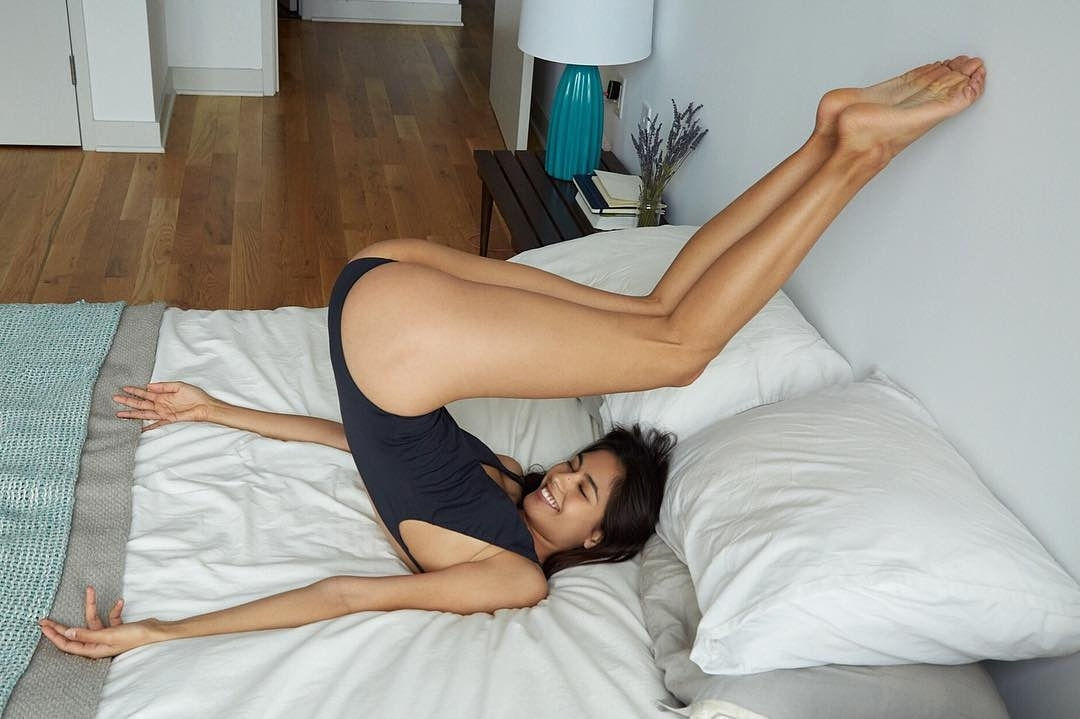 Flexible Brunette in swimsuit on her bed