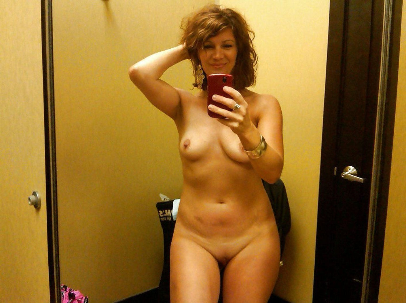 Brunette MILF with small titted takes naked selfie in mirror