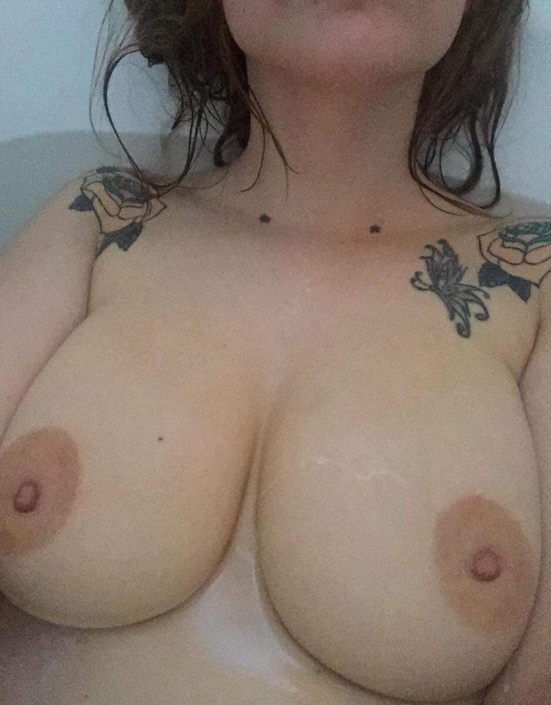 Sexy female displays perfect breasts in a bathtub