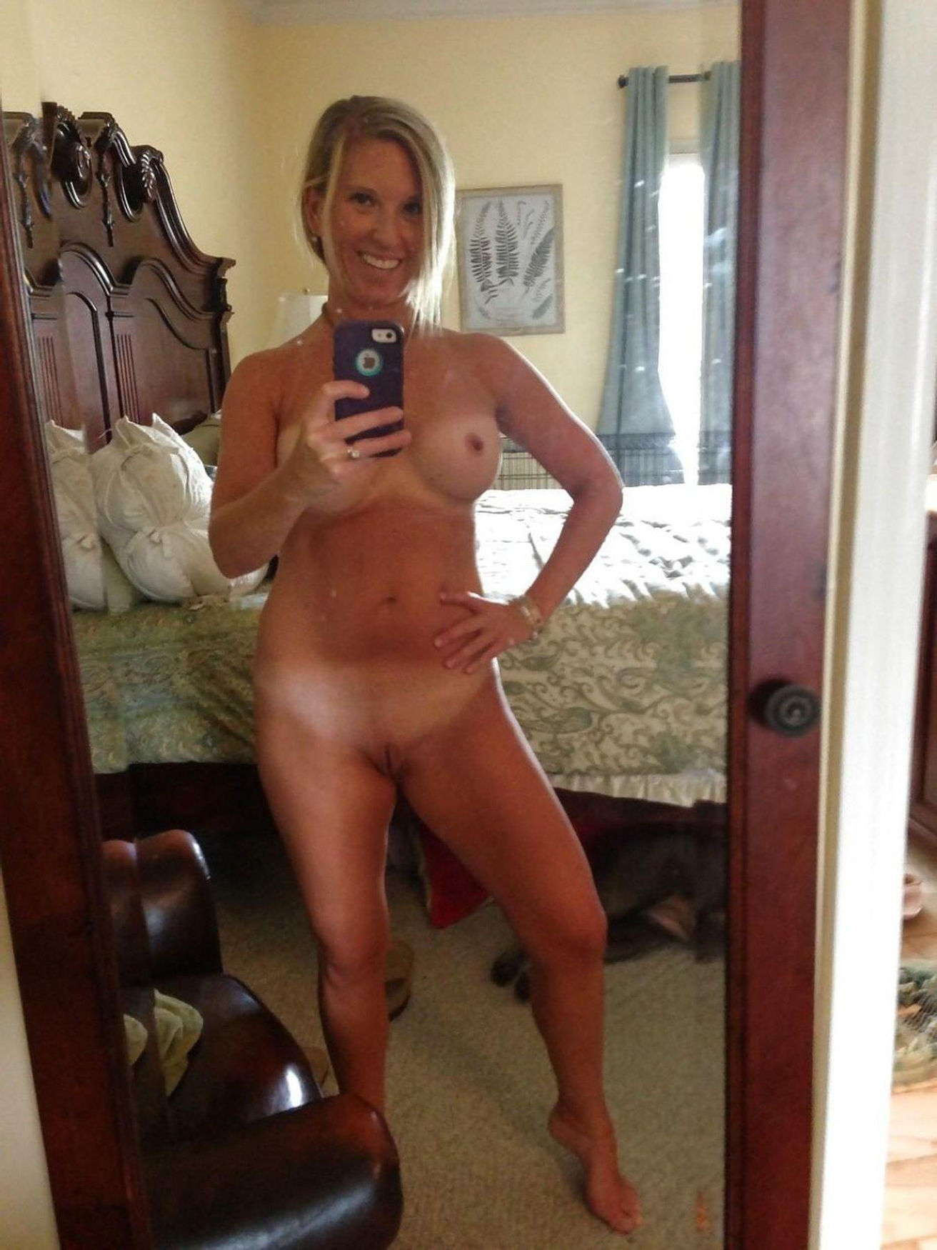 Middle aged dame shows off her shaved pussy after doffing bra and undies