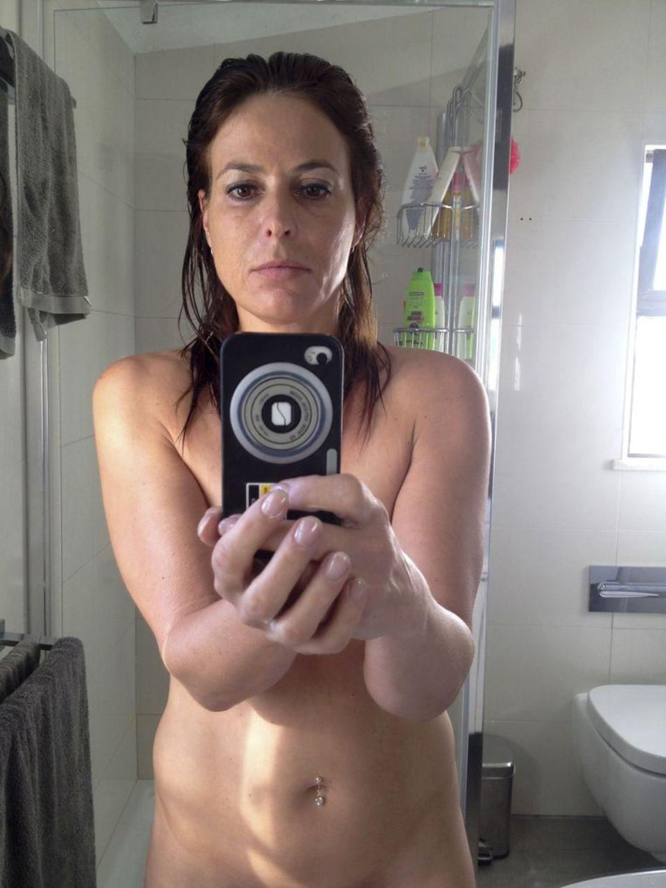 Naked wife make selfie of her natural body in bathroom mirror