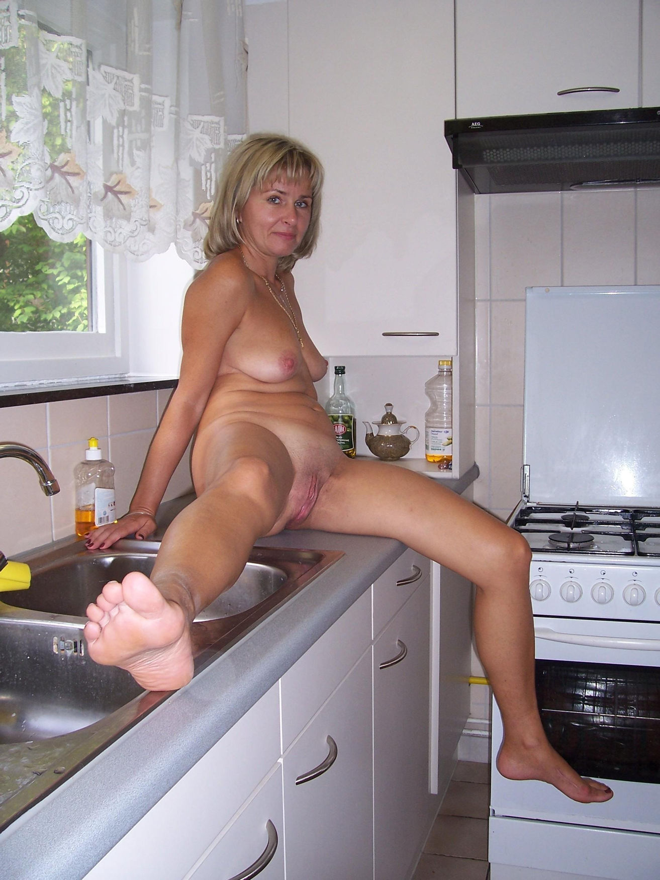 Hot wife spreads legs her naked pussy in the kitchen